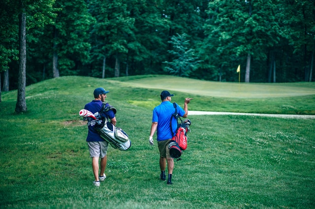 A golfer and caddy walking on a golf course